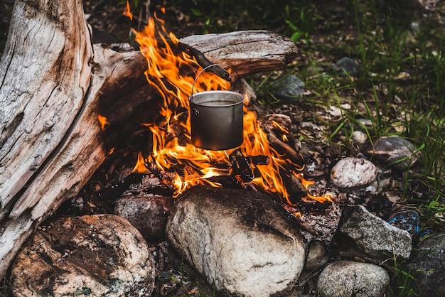Wasserkocher über feuer hängen. Premium Fotos