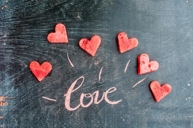 Wassermelone in herzform geschnitten. inschrift liebe mit kreide. valentinstag konzept. Premium Fotos