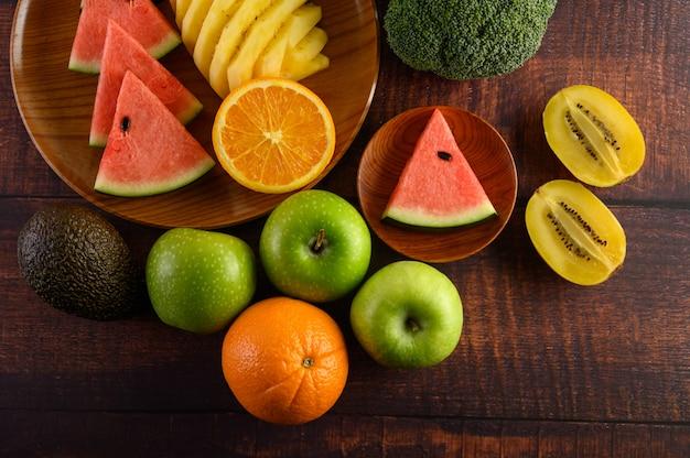 Wassermelone, orange, ananas, kiwi in scheiben geschnitten mit äpfeln und brokkoli auf einem holzteller und holztisch. Kostenlose Fotos