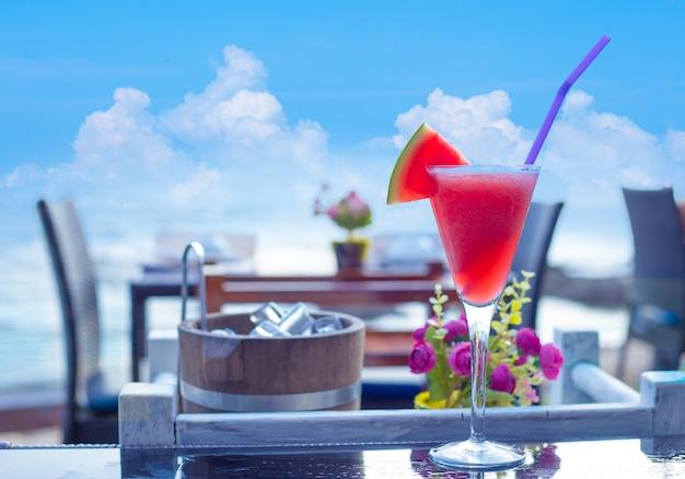 Wassermelone smoothie auf dem tisch am strand Premium Fotos