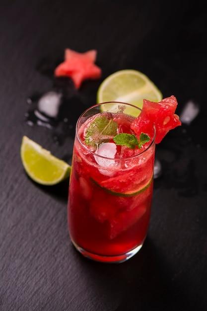 Wassermelone und kalk frisch in den hohen gläsern verziert durch wassermelonensterne auf schwarzer steintabelle Premium Fotos
