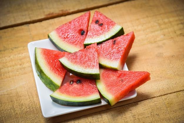 Wassermelonenscheibe auf weißer plattensommerfrucht auf hölzernem Premium Fotos