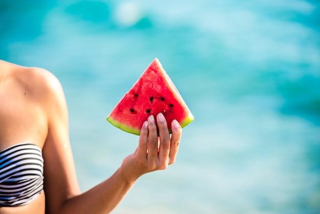 Wassermelonenscheibe in frauenhand über meer Premium Fotos