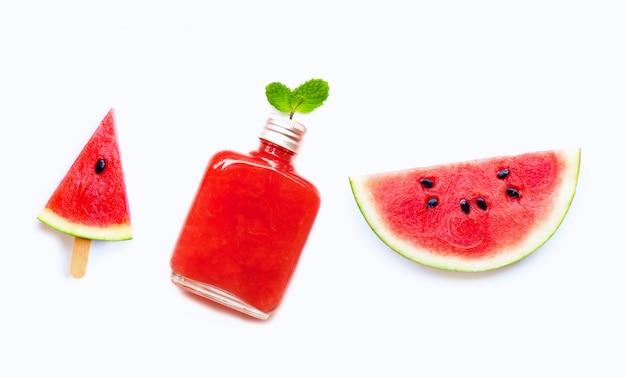 Wassermelonenscheibe und -eis am stiel mit der flasche gesundem wassermelonensaft lokalisiert auf weiß Premium Fotos