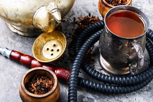 Wasserpfeife, die mit tee raucht Premium Fotos