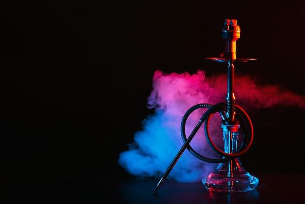 Wasserpfeife mit einer glasflasche und einer metallschale shisha mit farbigem rauch auf dem tisch Premium Fotos