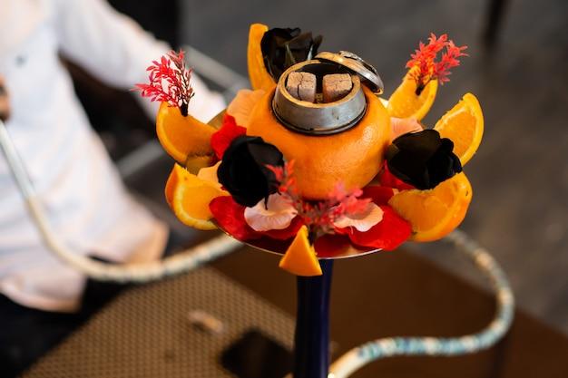 Wasserpfeife mit orangefarbenen, schwarzen rosen und anderen blumen verziert Kostenlose Fotos