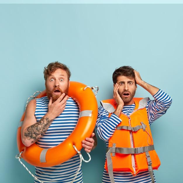 Wasserrettungskonzept. verlegene männliche rettungsschwimmer starren verwirrt in die kamera, tragen einen matrosenpullover und eine orangefarbene sicherheitsweste Kostenlose Fotos