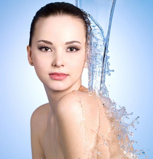 Wasserstrahl, der auf die junge frau mit schöner hautblauer wand fällt Kostenlose Fotos