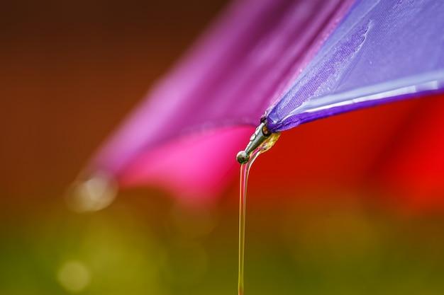 Wassertropfen laufen vom regenschirm herunter. Premium Fotos