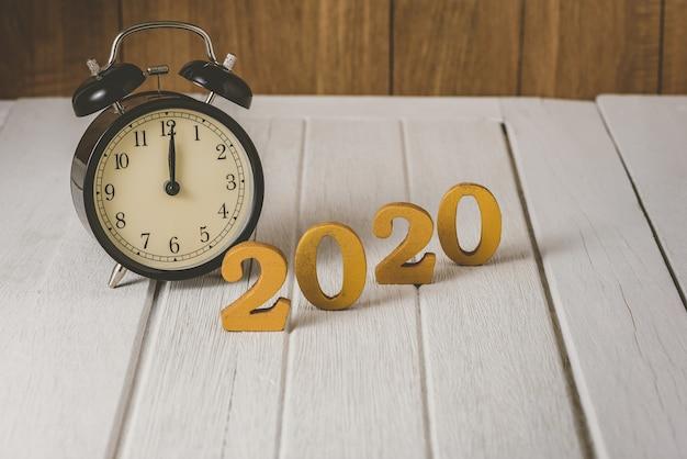 Wecker 2020 holzgoldzahl. frohes neues jahr auf natur-konzept Premium Fotos