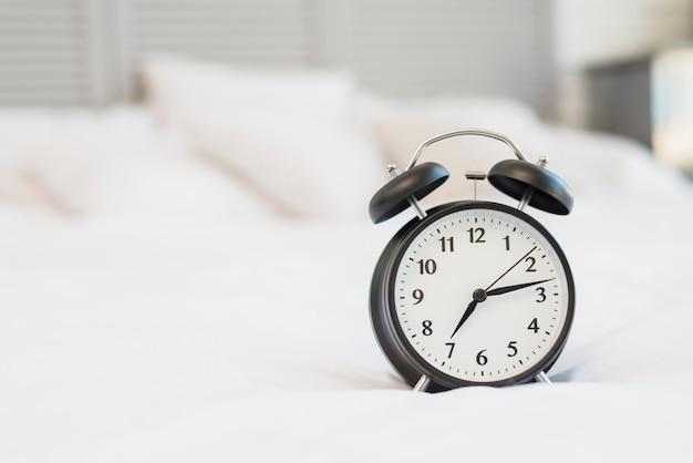 Wecker auf dem bett mit weißer bettwäsche Kostenlose Fotos