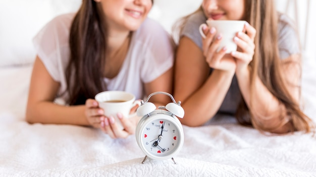 Wecker auf dem bett mit zwei frauen Kostenlose Fotos