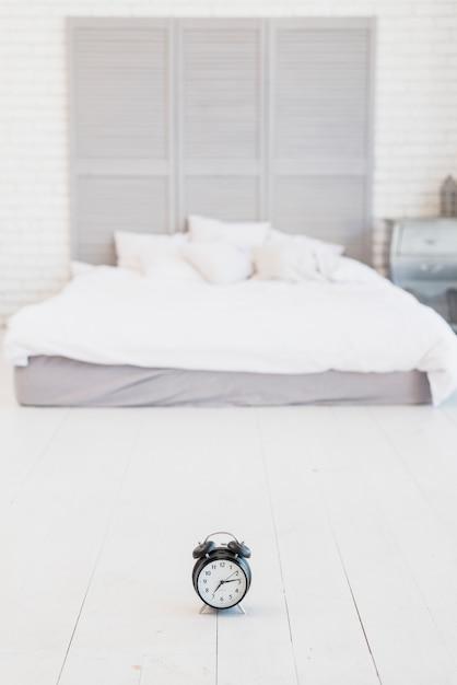 Wecker auf dem boden in der nähe von bett mit weißer bettwäsche Kostenlose Fotos