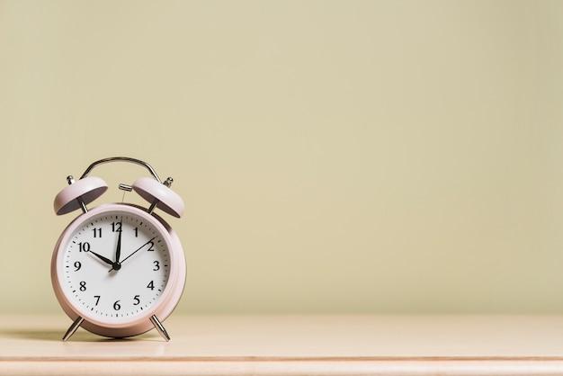 Wecker auf hölzernem schreibtisch, der die zeit 10 'o gegen farbige wand zeigt Kostenlose Fotos