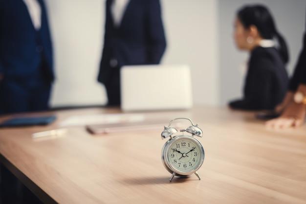 Wecker auf tisch mit geschäftsleuten im seminarraum. treffen des unternehmenserfolgs brainstorming-teamwork Premium Fotos