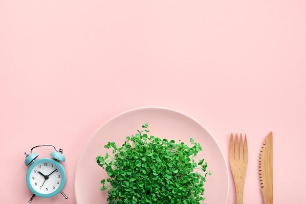 Wecker, besteck und teller mit grün auf rosa. Premium Fotos