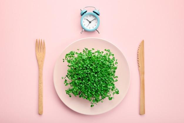Wecker, besteck und teller mit viel grün. Premium Fotos