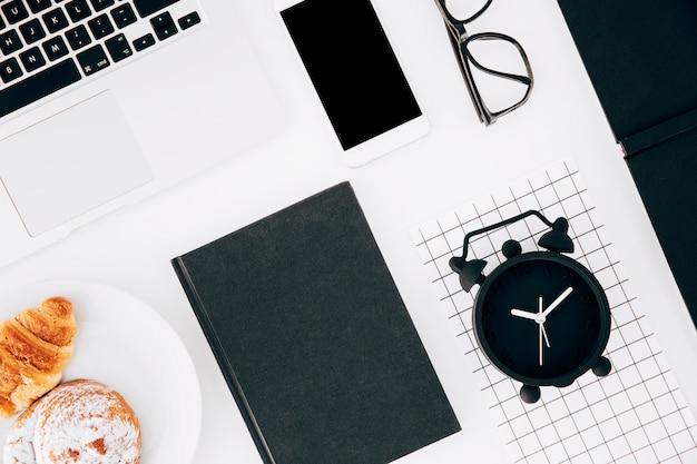 Wecker; laptop; handy; brille; gebackenes hörnchen und brötchen auf platte und tagebuch über weißem hintergrund Kostenlose Fotos