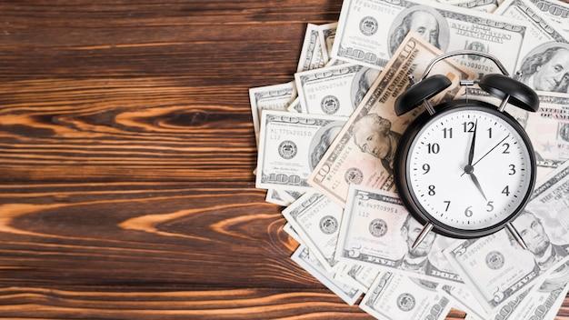Wecker über hundert dollar-banknoten auf hölzernem strukturiertem hintergrund Kostenlose Fotos