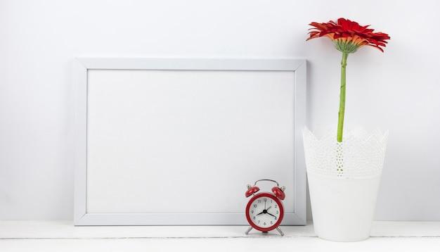 Wecker- und gerberablume mit leerem rahmen auf schreibtisch Kostenlose Fotos