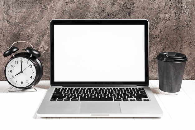 Wecker und wegwerfkaffeetasse mit einem offenen laptop auf weißem schreibtisch Kostenlose Fotos