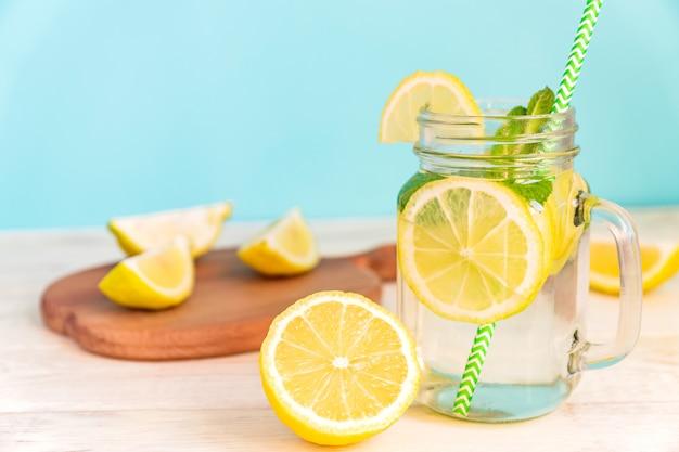 Weckglasglas selbst gemachte limonade mit zitronen-, minzen- und grünbuchstroh auf hölzerner rustikaler tabelle und blauem hintergrund. Premium Fotos