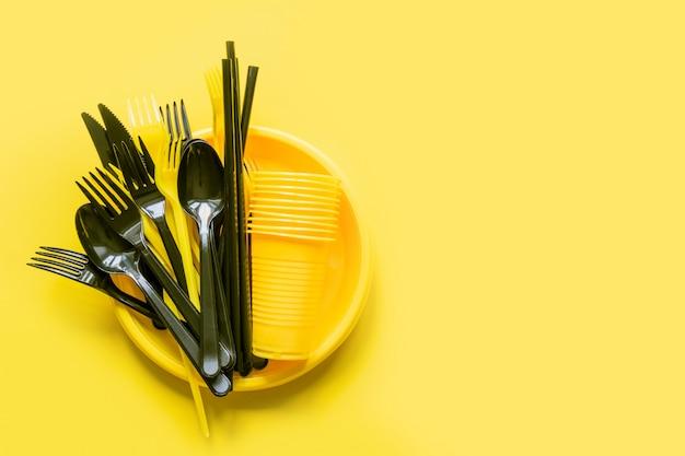 Wegwerfpicknickschwarzgeschirr auf gelb. Premium Fotos