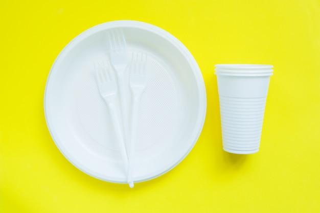 Wegwerfplastikgeschirr auf heller gelber oberfläche Premium Fotos