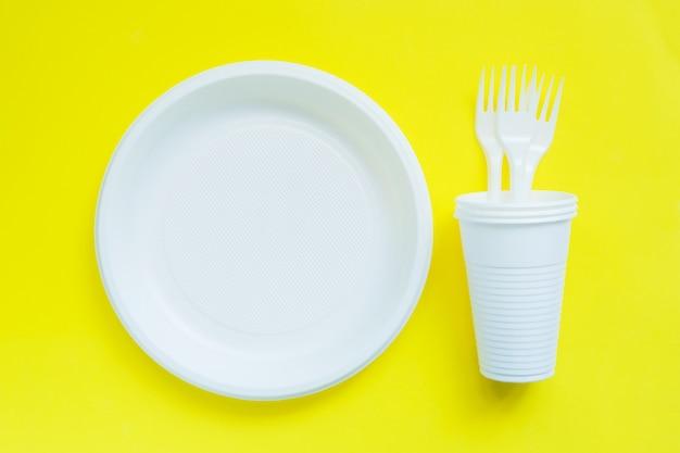Wegwerfplastikgeschirr auf heller gelber tabelle mit kopienraum. Premium Fotos