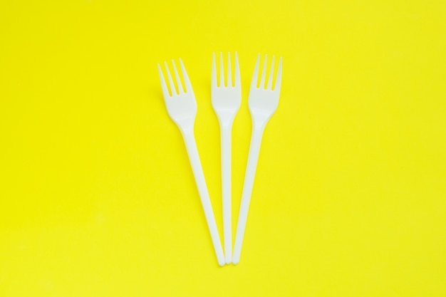 Wegwerfplastikstecker auf hellem gelbem hintergrund mit kopienraum. Premium Fotos