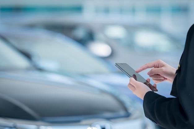 Weibliche autoverkäufer nutzen mobile smartphones in autohäusern Premium Fotos