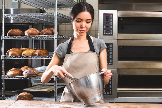 Weibliche bäckerarbeitskraft, die den teig in rührschüssel an der bäckerei zubereitet Kostenlose Fotos