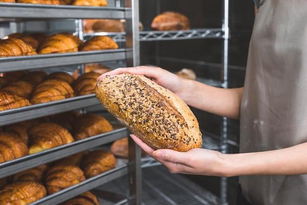 Weibliche bäckerhand, die frischen brotlaib hält Kostenlose Fotos