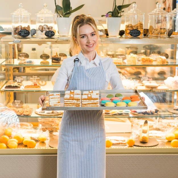 Weibliche bäckerholding backte frische makronen und gebäck im behälter Kostenlose Fotos