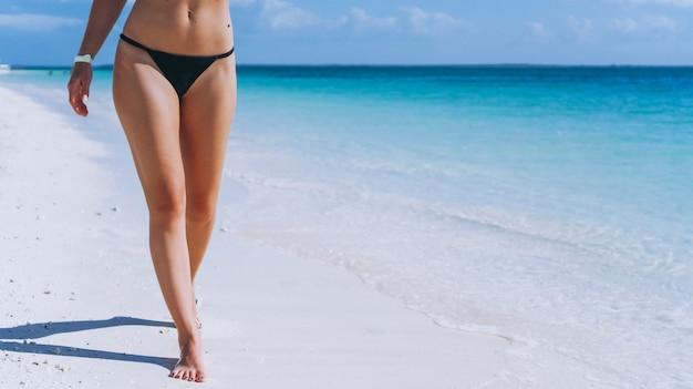 Weibliche beine, die auf sand durch den ozean gehen Kostenlose Fotos