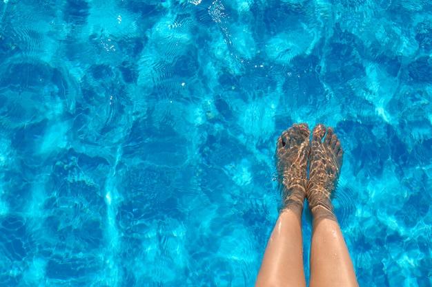 Weibliche beine im poolwasser im sommer Premium Fotos