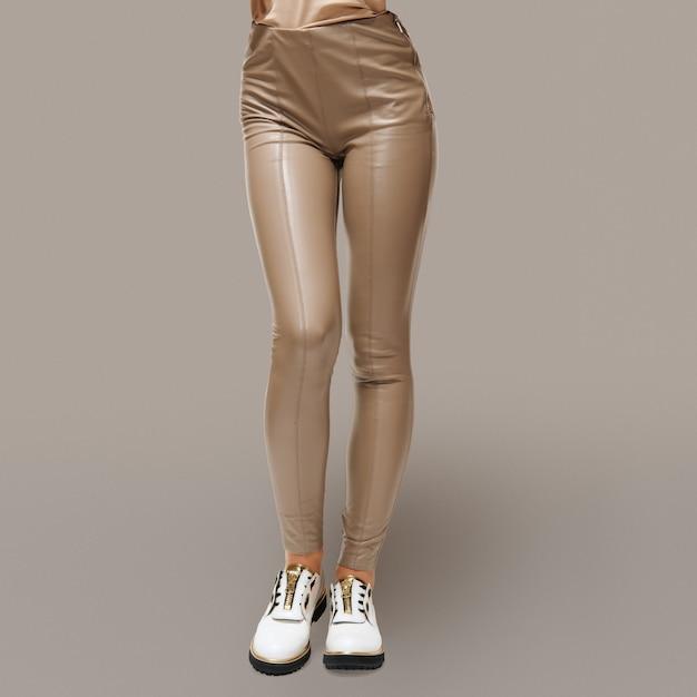 Weibliche beine in beige kunstlederhose und grobe stiefel mit gerillter laufsohle Premium Fotos