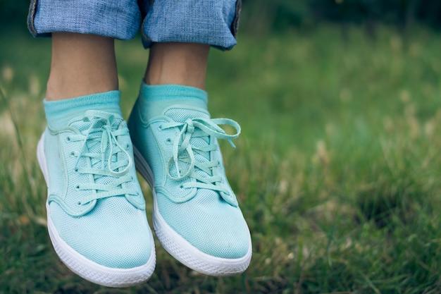 Weibliche beine in den jeans und in sportschuh, die in die luft über dem grünen gras im park schwimmen Premium Fotos