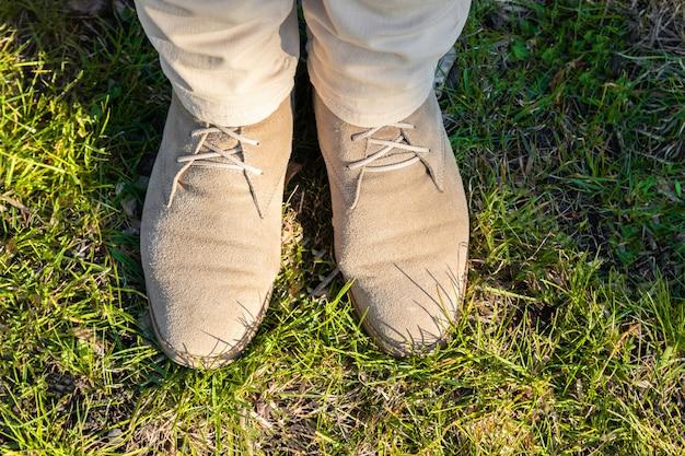 Weibliche beine in der hellen hose mit beige schuhen auf grünem gras an einem sonnigen tag Premium Fotos