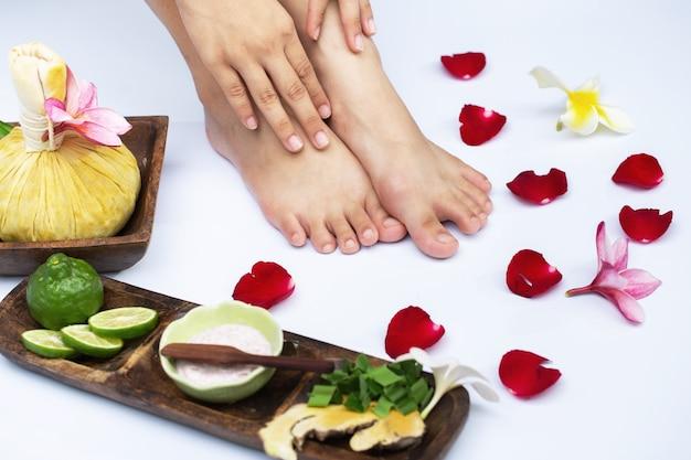Weibliche beine in der wasserdekoration die blumen frau, die eine pedikürebehandlung an einem badekurort oder an einem schönheitssalon mit dem pediküristmassieren hat Premium Fotos