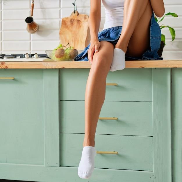Weibliche beine in socken auf küchentisch Premium Fotos