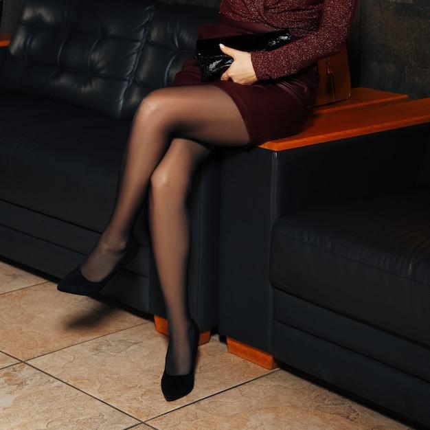 Weibliche beine in strumpfhosen auf ledersofa Premium Fotos