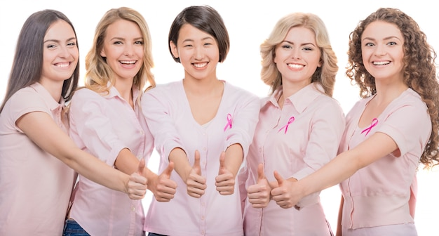 Weibliche brustkrebsteilnehmer, die oben daumen gestikulieren. Premium Fotos