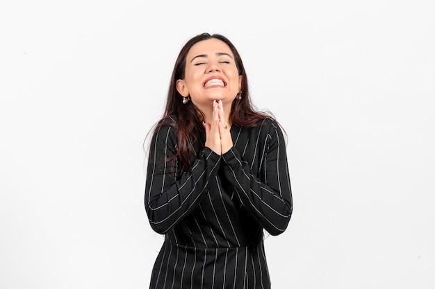 Weibliche büroangestellte im strengen schwarzen anzug, der auf weiß aufwirft Kostenlose Fotos