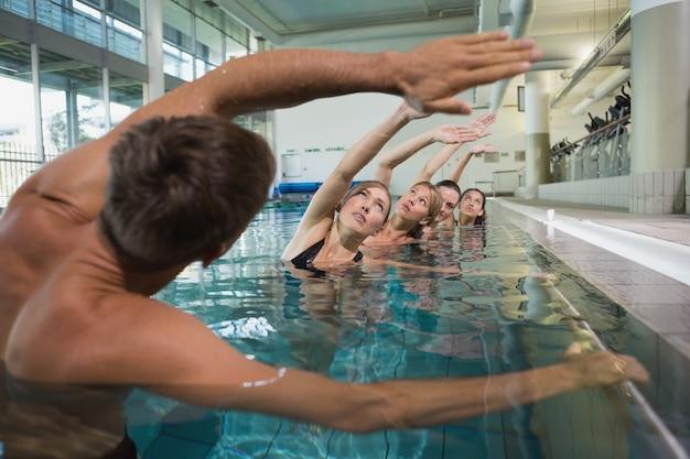 Weibliche eignungsklasse, die aqua aerobic mit männlichem lehrer tut Premium Fotos