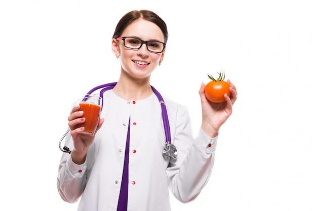 Weibliche ernährungswissenschaftler-grifftomate im abschnitt und glas saft in ihren händen auf weiß Premium Fotos