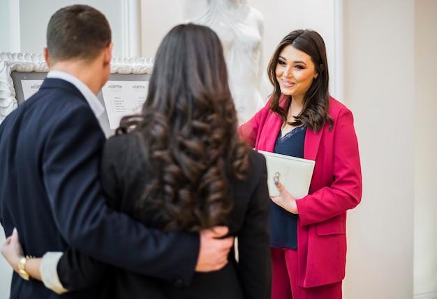 Weibliche event manager und paar reden Kostenlose Fotos