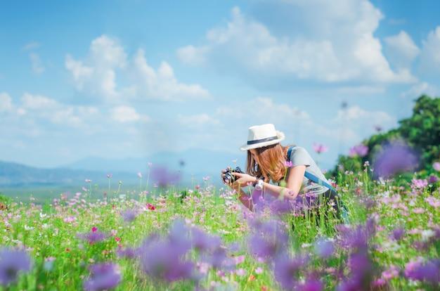 Weibliche fotografie mit der kamera, die ein foto der blume macht Premium Fotos