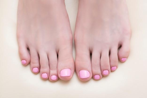 Weibliche füße mit einer rosa pediküre Premium Fotos